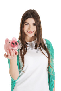 Young casual woman holding piggy-bank.
