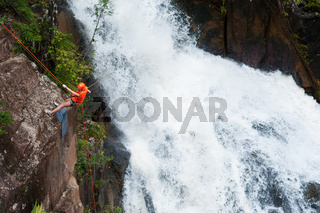 tourist abseils into Datanla waterfall in Vietnam