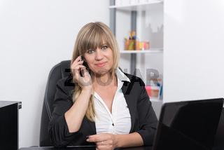 Frau telefoniert am Empfangstresen