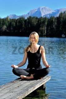 Junge Frau macht Yoga am Hintersee