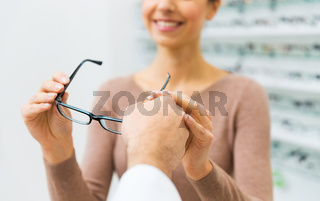 close up of woman with glasses at optics store