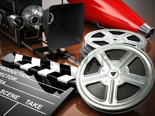 Video, movie, cinema vintage concept. Retro camera, reels and clapperboard.