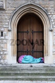 London, Obdachloser im Schlafsack vor Tor