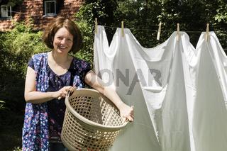Frau beim Wäscheaufhängen im Garten, Hanging up the washing in a garden