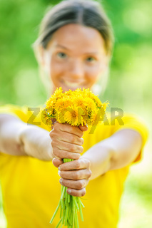 young woman in with bouquet of dandelions