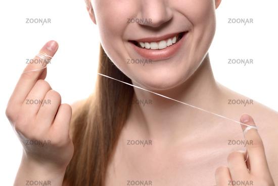Frau mit gesunden weißen Zähnen benutzt Zahnseide