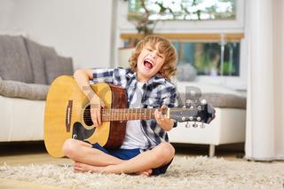 Junge hat Spaß beim Singen zur Gitarre