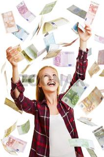 Junge Frau steht in Regen aus Geldscheinen