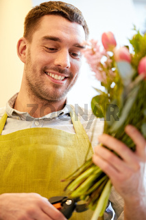 smiling florist man making bunch at flower shop