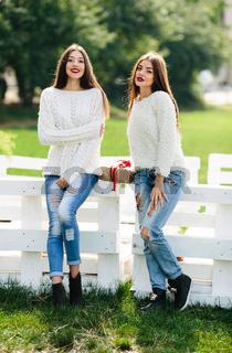 Two girls lean bench