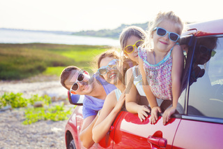 Portrait of a smiling family with two children at beach in the car