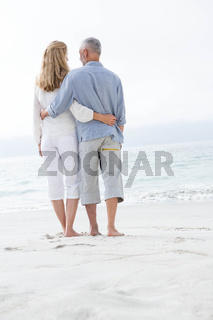 Happy couple hugging each other and looking at the sea