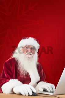 Composite image of santa surfs on the internet