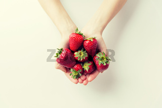 close up of woman hands holding strawberries