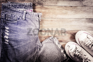 Jeans and sneakers on a wood background.