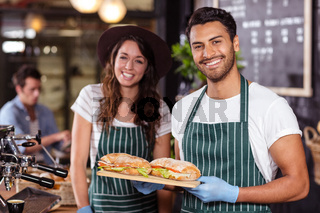 Smiling baristas holding sandwiches