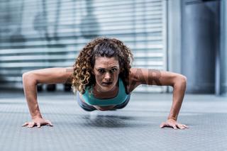Attentive muscular woman doing pushups