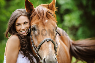 portrait of young smiling woman with horse