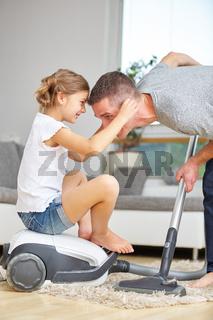 Vater und Mädchen mit Staubsauger haben Spaß