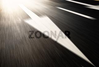 asphalt road with traffic signs under light