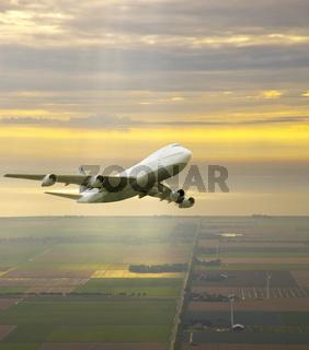 Airplane flying in beautiful yellow sky