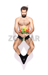 a young man with a beard and flowers jumping in the studio on a