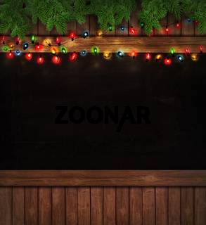 Christmas lights on wooden blackboard