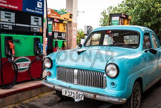 Blauer amerikanischer Oldtimer an der Tankstelle in Havanna Kuba