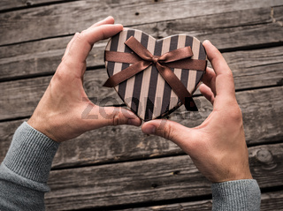 Heart shaped gift box in man#39;s hands.
