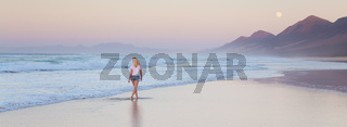 Lady walking on sandy beach in sunset.