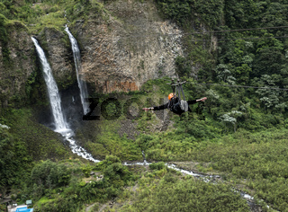 Tourist gliding on the zip line trip against Bridal veil (Manto de la novia), waterfall in Cascades route, Banos, Ecuador