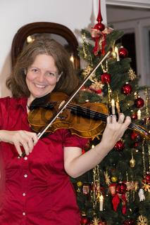Frau musiziert auf einer Geige zu Weihnachten