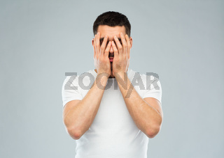 man in white t-shirt covering his face with hands