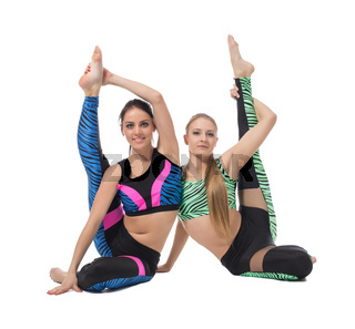 Pretty gymnasts posing while doing vertical split