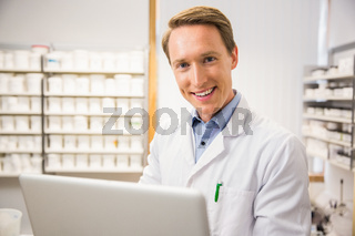 Happy pharmacist using his laptop