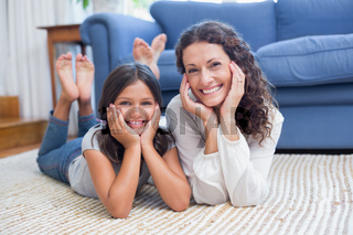 Happy mother and daughter lying on the floor