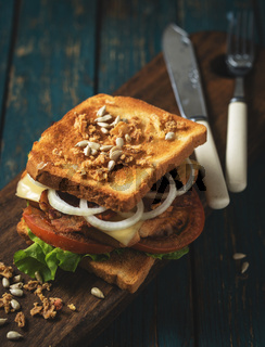 Sandwich with tomato, onions and bacon on a vintage wooden background in rustic style