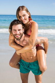 Man giving piggy back ride to woman