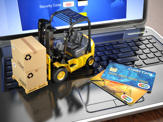 Concept of delivering, shipping or logistics. Forklift on laptop keyboard and credit cards.