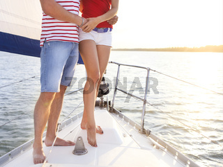 Feet of a couple on sailboat deck in the sea. Sunset