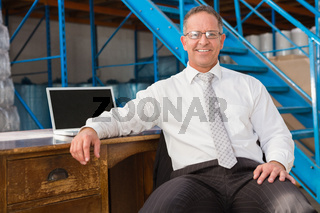 Smiling warehouse manager with computer