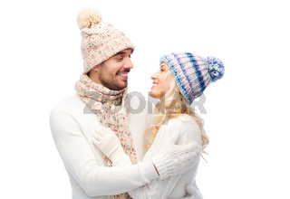smiling couple in winter clothes hugging