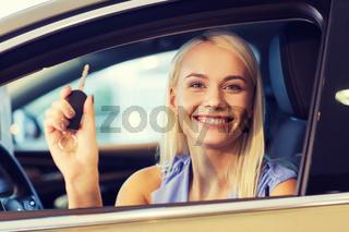 happy woman getting car key in auto show or salon