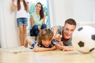 Vater und Junge haben Spaß und spielen mit Fußball
