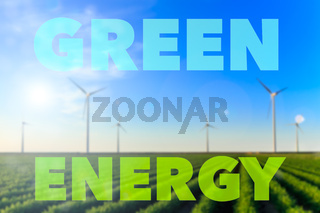Blurred image of windmills at sunset at a field of crops. Text green energy small lens flare.