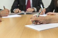 Hände mit Kugelschreiber auf einem Schreibtisch