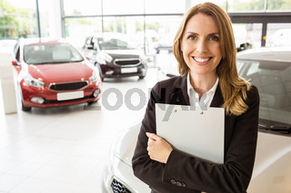 Smiling saleswoman holding document while looking at camera