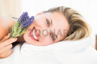 Beautiful blonde lying on massage table with lavanda
