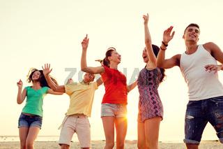 smiling friends dancing on summer beach