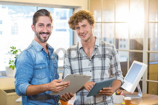 Smiling business team holding clipboard and tablet